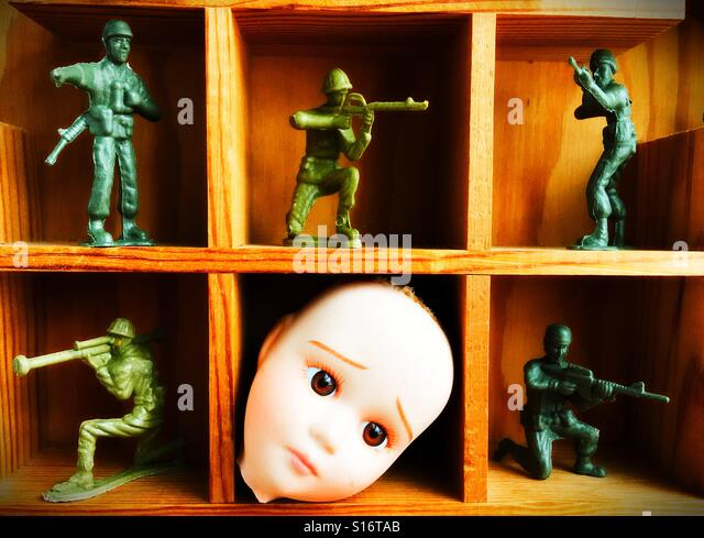 A worried looking doll head surrounded by toy soldiers. - Stock Image