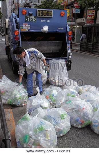 Japan Tokyo Ikebukuro garbage collection collector Asian man truck compactor plastic bags empty bottles recycling - Stock Image