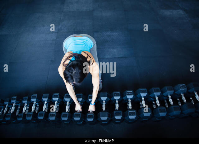 Woman takes a dumbbell at gym - Stock-Bilder