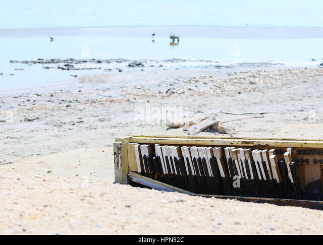 A broken piano carelessly discarded on the shore of the Salton Sea near Bombay Beach in California, USA. - Stock Image