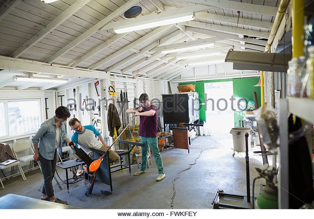 Glassblowers blowing molten glass in workshop - Stock Image