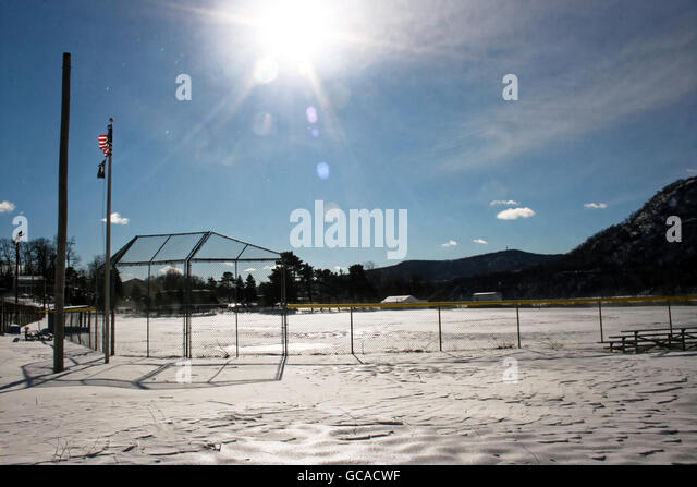 Snow covered baseball field with intense sunshine. - Stock Image