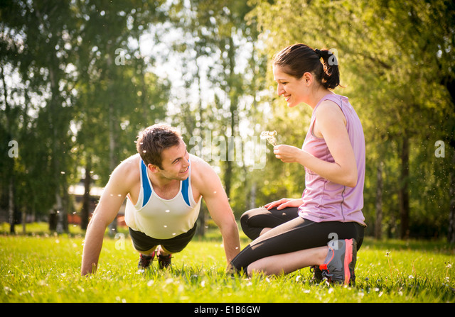 Man making push-ups while woman is blowing dandelion seeds on him - outdoor in nature - Stock Image