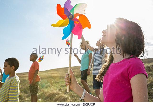 Schoolchildren holding pinwheels up outdoors - Stock Image