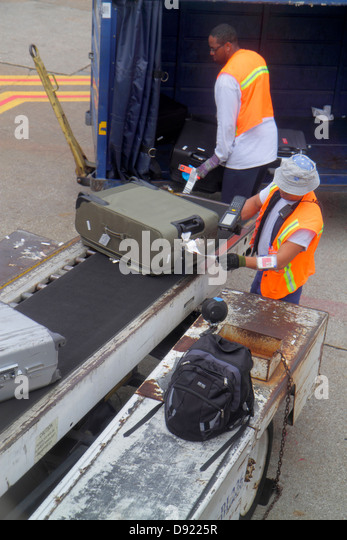 Texas Houston George Bush Intercontinental Airport IAH Black man employee baggage handler conveyor belt tarmac luggage - Stock Image