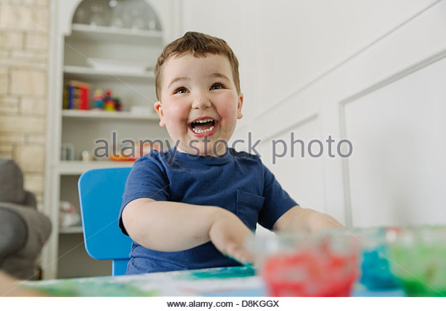 Laughing boy finger painting at home - Stock Image