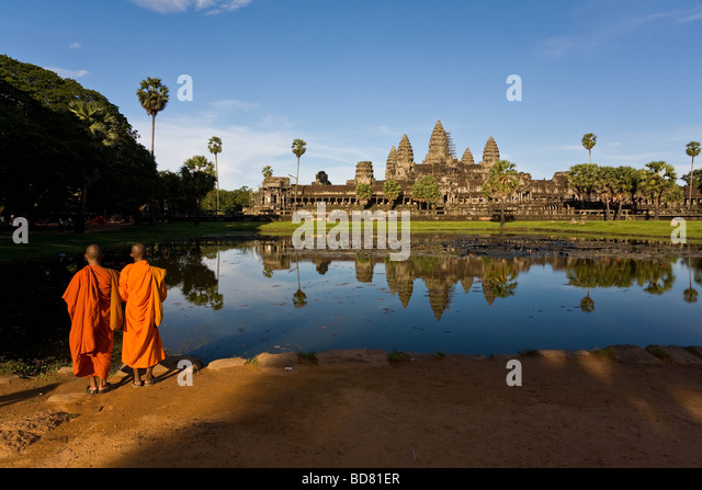 Classic view of Angkor Wat across the pools with a clear reflection, with two orange-robed monks in the foreground - Stock-Bilder