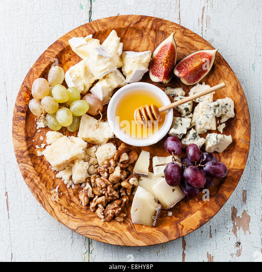 Cheese plate Assortment of various types of cheese on olive wood plate - Stock Image