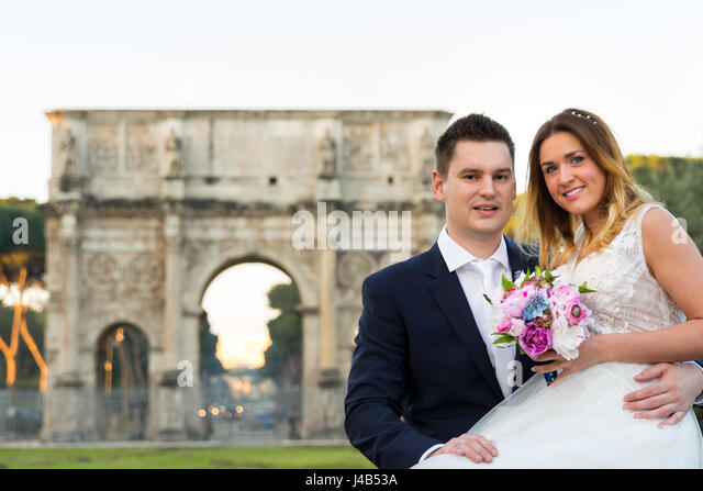 Bride and groom wedding poses, Arco di Costantino in the background, Rome, Italy - Stock Image