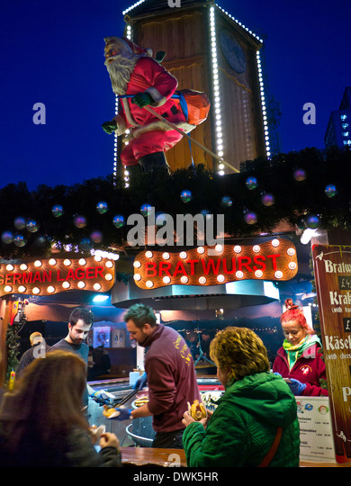 German Christmas market food stall illuminated at night South Bank London UK - Stock Image