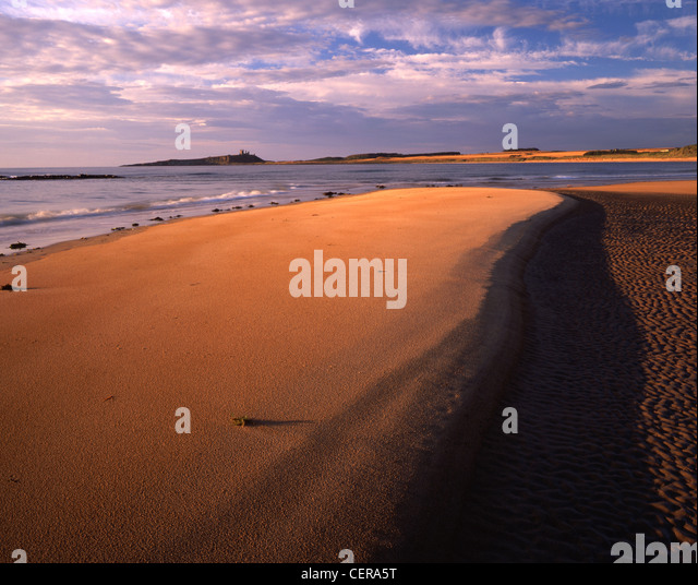 The ruins of Dunstanburgh Castle form the perfect backdrop for the beautiful sands of Embleton Bay. Dunstanburgh - Stock Image