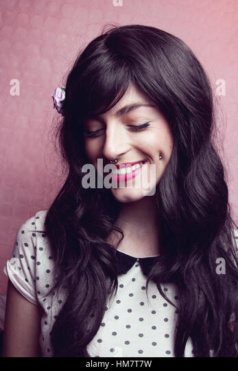 Portrait of a pretty young woman with pink background - Stock Image