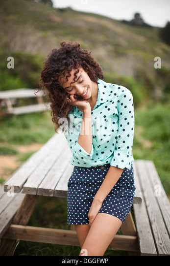 Young woman with hand in hair standing by picnic table, smiling - Stock Image