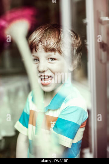 happy small boy standing by the window - Stock Image