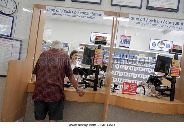 Miami Beach Florida Walgreens pharmacy drug store pharmacist filling prescription senior man customer English Spanish - Stock Image