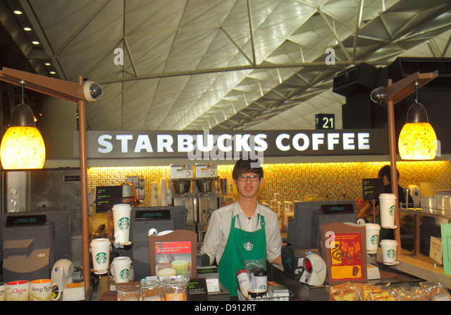 Hong Kong China International Airport HKG terminal concourse gate area Starbucks Coffee cafe Asian man employee - Stock Image
