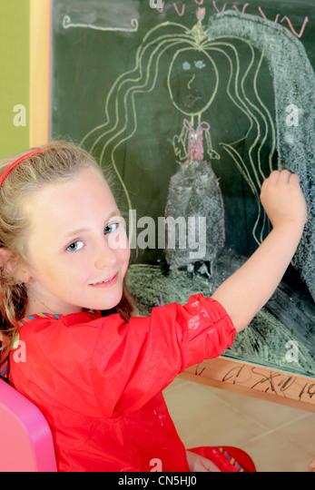 happy artistic,kid,drawing on blackboard in school or home - Stock Image