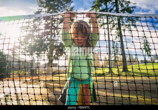 Girl standing on tennis court lifting net - Stock Image