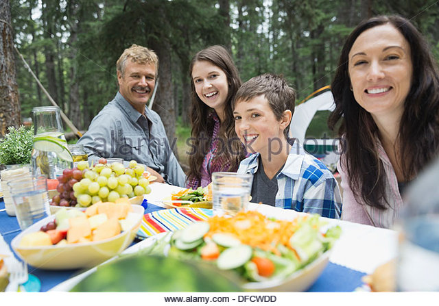 Portrait of happy family enjoying meal at campsite - Stock Image