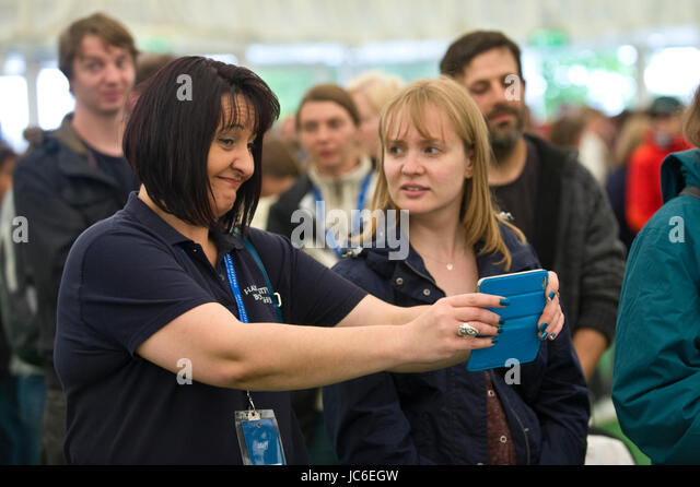 Woman taking photo on smartphone in bookshop at Hay Festival of Literature and the Arts 2017 Hay-on-Wye Powys Wales - Stock Image
