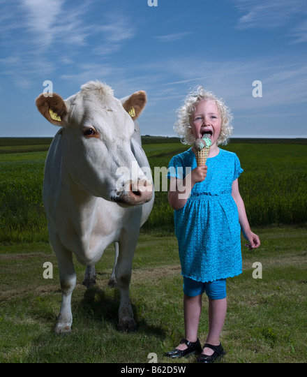 Young girl eating an Ice cream cone with white dairy cow, Eastern Iceland - Stock Image