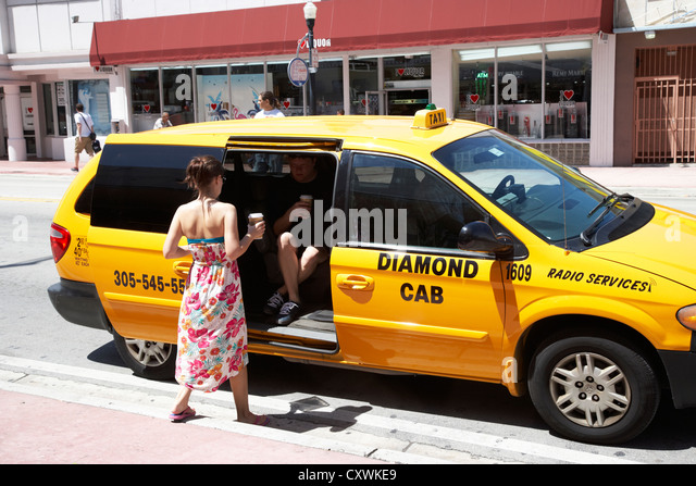 couple getting into minivan yellow cab taxi with coffees in miami south beach florida usa - Stock Image