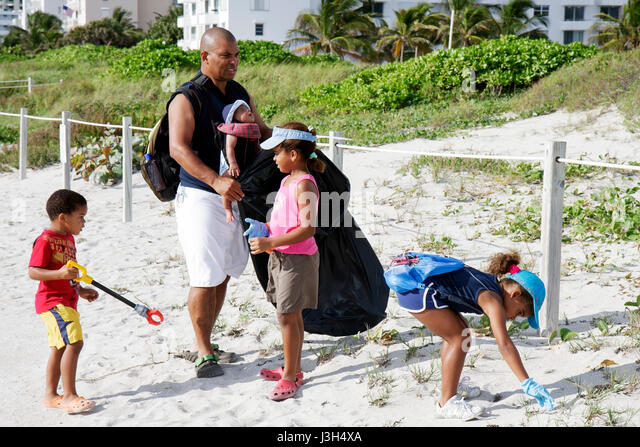 Miami Beach Florida Lummus Park International Coastal Cleanup volunteers Black man baby girls boy family father - Stock Image