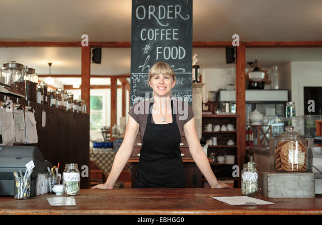 Portrait of female shop assistant in country store cafe - Stock-Bilder