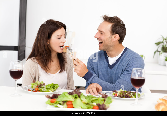 Attentive man giving a tomato to his girlfriend while having lunch - Stock-Bilder