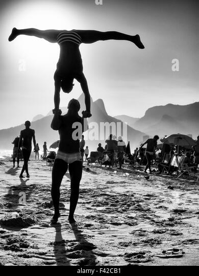 Silhouettes making acrobatic poses in front of a black and white sunset beach scene at Ipanema Beach Rio de Janeiro - Stock Image