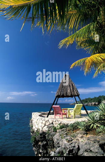 Jamaica Negril Caribbean Colorful Chairs With Overhead Palms by the Water - Stock Image