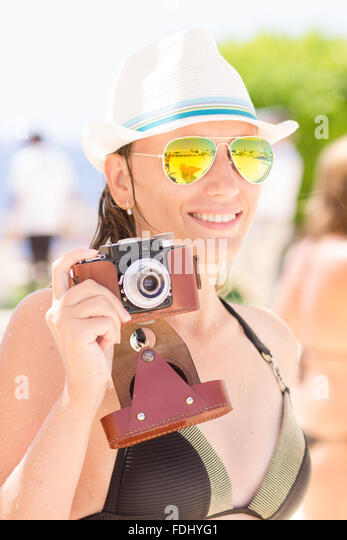 Young happy woman in black bikini having fun with old photo camera at the summer beach holidays. - Stock-Bilder