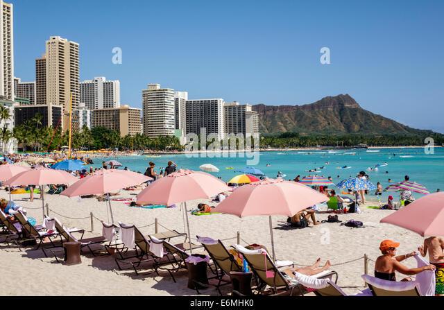 Waikiki Beach Honolulu Hawaii Hawaiian Oahu Pacific Ocean Royal Hawaiian hotel pink umbrellas Diamond Head Crater - Stock Image