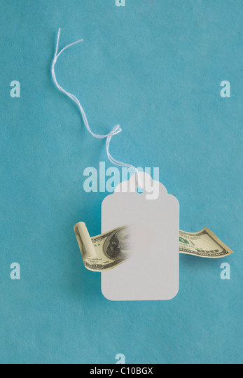 white price tag with 100$ dollar bill dissolving through it. - Stock Image