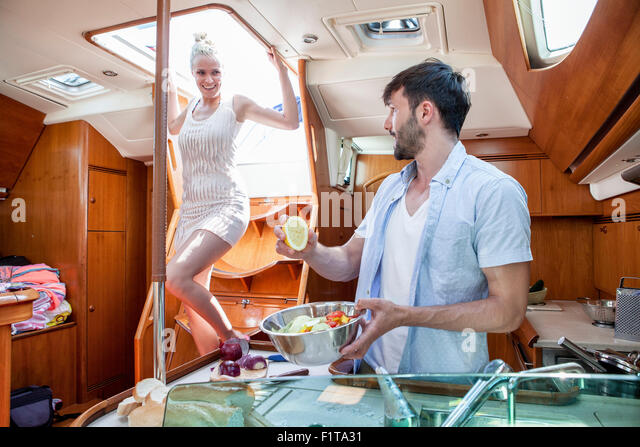 Young couple cooking in galley of yacht,, Adriatic Sea - Stock Image