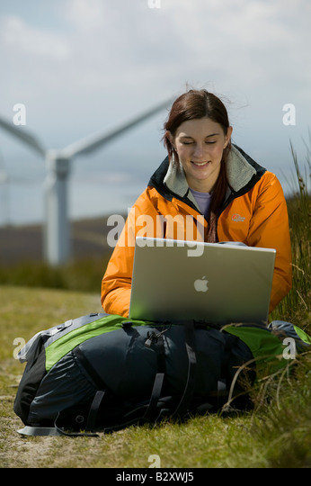 Female with laptop and wind turbine in background - Stock Image