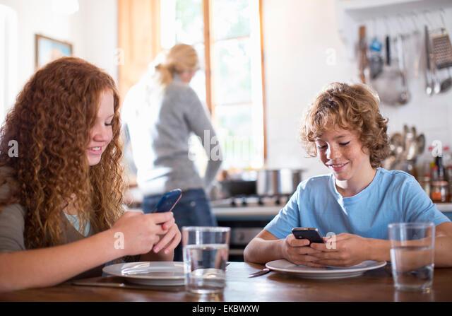 Siblings using smartphone at dining table - Stock-Bilder
