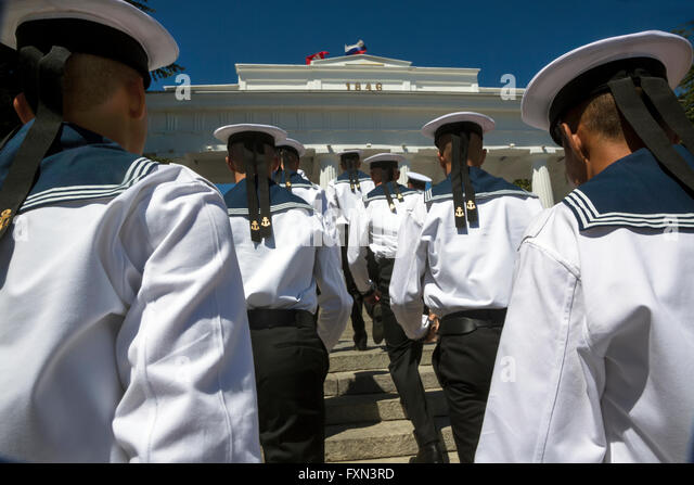 Black Sea Fleet sailors go to columned entrance to the Grafs Promenade on the Sevastopol waterfront, Crimea Republic - Stock Image