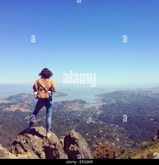 USA, California, Marin County, Mill Valley, Young woman standing on mountain overlooking San Francisco - Stock-Bilder