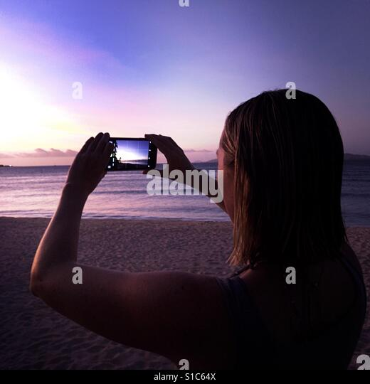 A young woman take a photo of the sunset with her smart phone. Tavarua Island, Fiji. - Stock Image