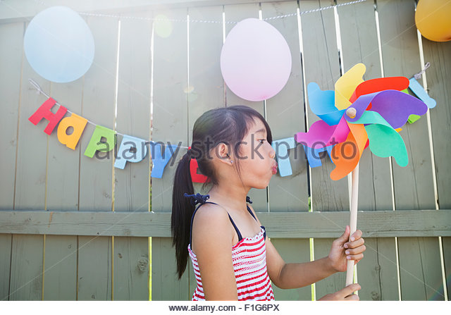 Girl blowing pinwheel at backyard birthday party - Stock Image