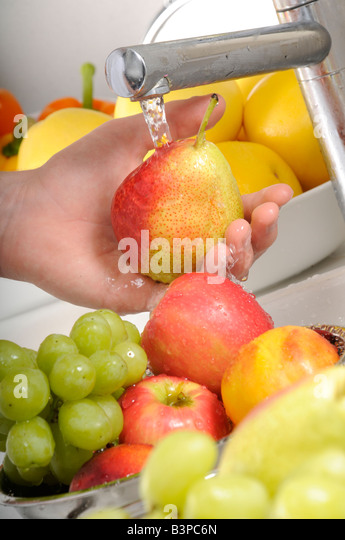 WOMAN WASHING PEAR AT KITCHEN SINK - Stock Image