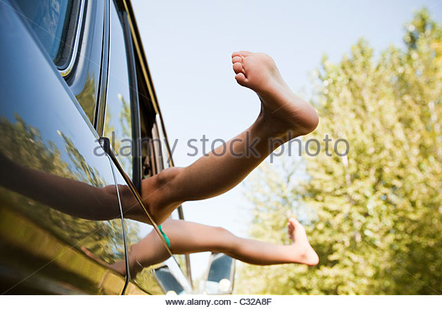 Legs sticking out of a car window - Stock Image