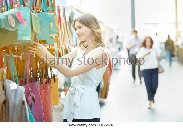 Young woman shopping for handbag at street market. - Stock Image