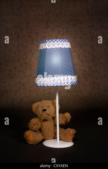 a teddy bear is sitting under an old vintage lamp - Stock Image