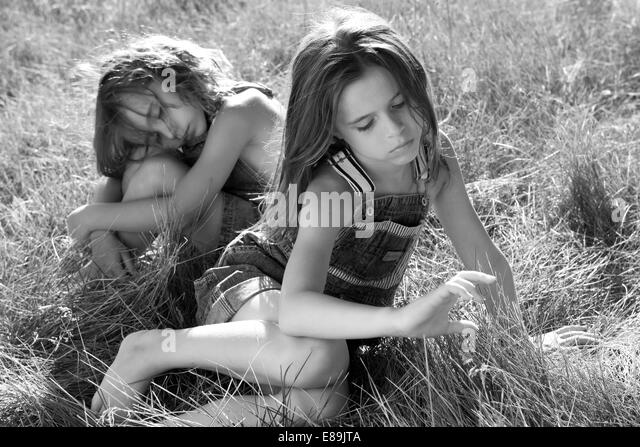 Girls in overalls in field of tall grass - Stock-Bilder