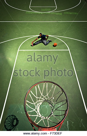 A basketball player stretches before a game. - Stock Image
