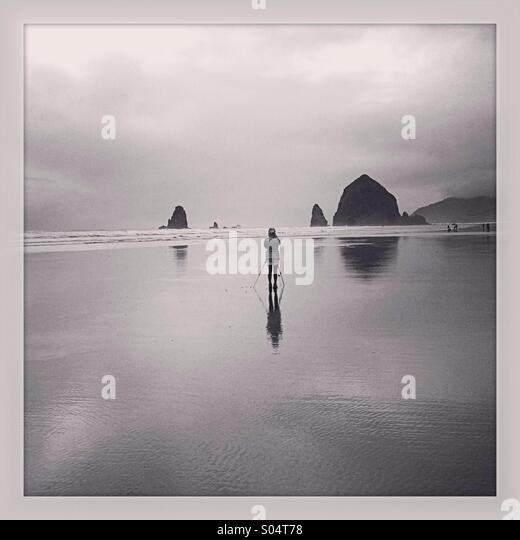 Photographer takes aim at Haystock Rock near Cannon Beach, OR. - Stock Image