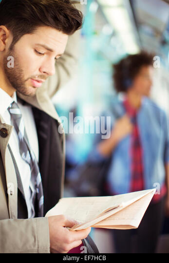Businessman reading newspaper on train - Stock Image