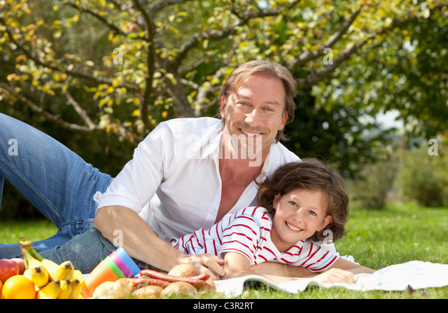 Germany, Bavaria, Father and daughter (8-9 Years) having fun at picnic, smiling - Stock Image